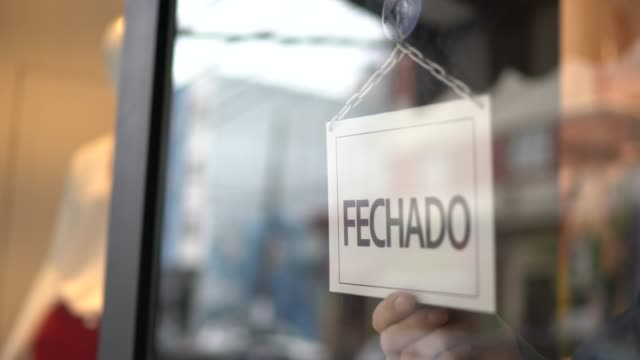 vídeos de stock e filmes b-roll de business owner turning to closed sign (fechado) on storefront door - turning
