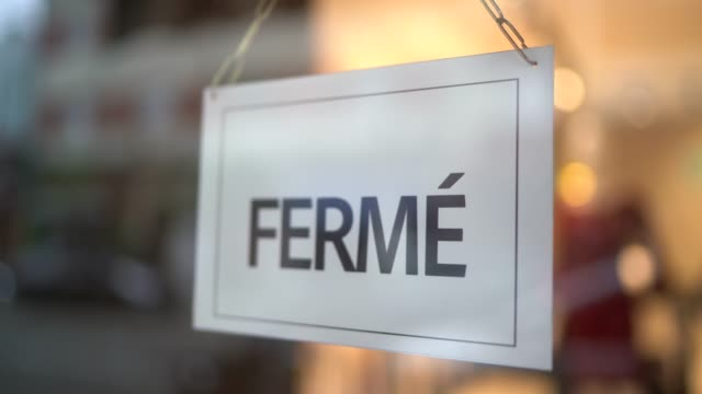 business owner turning to closed sign (fermé) on storefront door - french culture stock videos & royalty-free footage