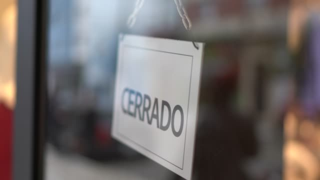 business owner turning to closed sign (cerrado) on storefront door - placard stock videos & royalty-free footage