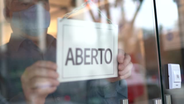 business owner turning to open sign (aberto) on storefront door - aberto stock videos & royalty-free footage