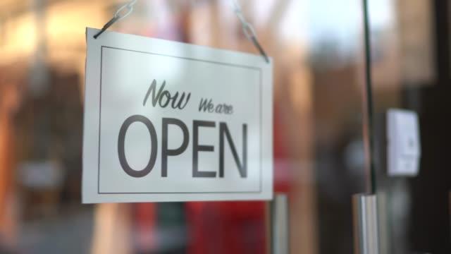 imprenditore che si rivolge all'open sign sulla porta del negozio - insegna di negozio video stock e b–roll