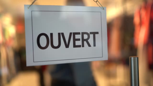 business owner turning to opened sign (ouvert) on storefront door - french language stock videos & royalty-free footage