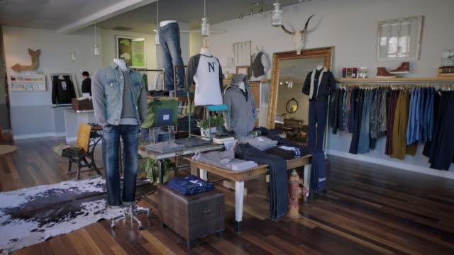 Business owner turns off the lights at end of day in clothing shop
