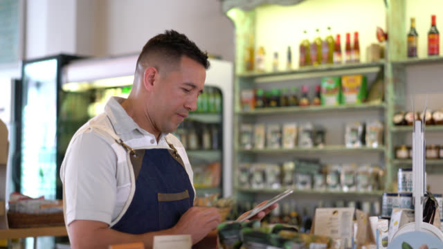 business owner using a computer tablet to make an inventory of the products at the food store - store stock videos & royalty-free footage