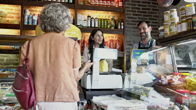 business owners conversing with senior customer in food shop - customer focused stock videos & royalty-free footage