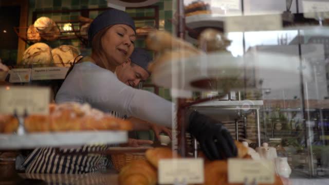 stockvideo's en b-roll-footage met bedrijfseigenaren van een bakkerij, man schoonmaak teller en vrouw het regelen van het brood display terwijl praten en glimlachen - winkeldisplay