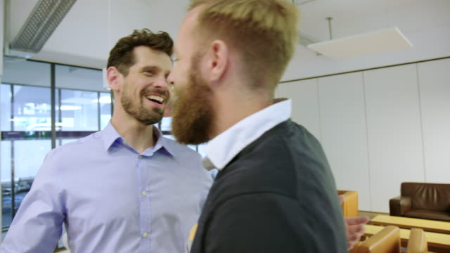 business partners greeting each other with a hug - mid adult men stock videos & royalty-free footage