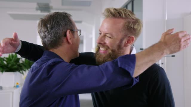 vídeos de stock e filmes b-roll de business partners looking happy with financial reports - colega de trabalho