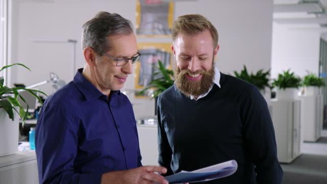 vidéos et rushes de partenaires commerciaux examinant un rapport - brainstorming
