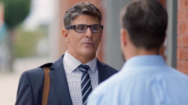 Business partners speak outside of restaurant