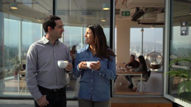 オフィステラスでコーヒーブレイクを取るビジネスパートナーが話し、笑顔 - casual clothing点の映像素材/bロール