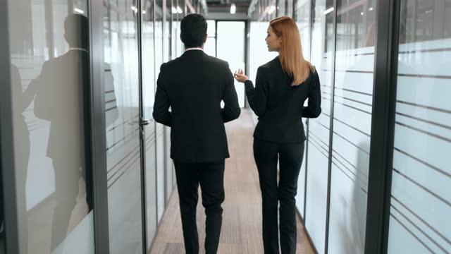vídeos de stock, filmes e b-roll de parceiros de negócios conversando em corredores de escritório - vínculo