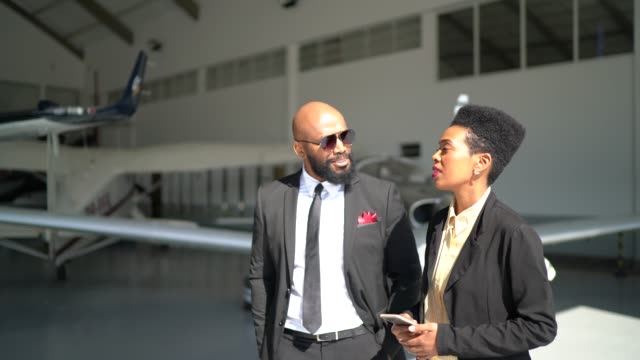 business partners using smartphone and talking while walking into a hangar - millionnaire stock videos & royalty-free footage
