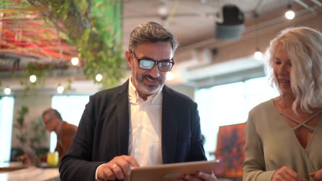 vídeos de stock, filmes e b-roll de parceiros de negócios andando e usando tablet digital no coworking - negócios finanças e indústria