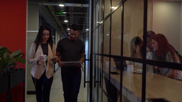 business partners walking down the corridor of a coworking office man reading a document and woman looking at smartphone - casual clothing stock videos & royalty-free footage