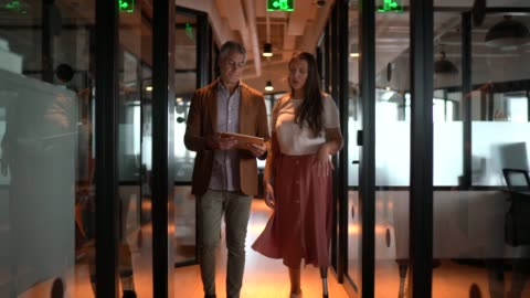 business partners walking using digital tablet at corridor - disability stock videos & royalty-free footage
