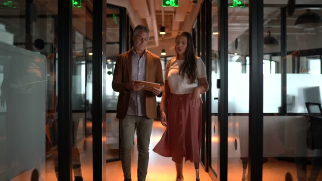 business partners walking using digital tablet at corridor - employee stock videos & royalty-free footage