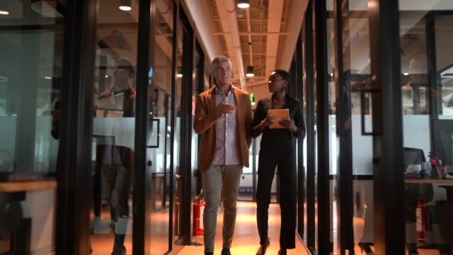 廊下でデジタルタブレットを使用して歩くビジネスパートナー - 決定点の映像素材/bロール