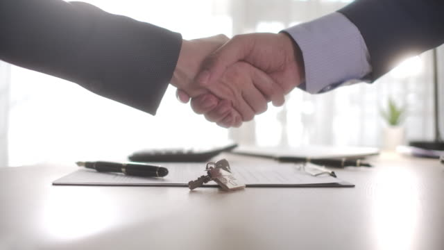 business partners with house keys handshake - market trader stock videos & royalty-free footage