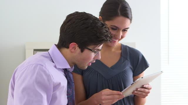 vídeos de stock e filmes b-roll de business partners working on a tablet - confiabilidade