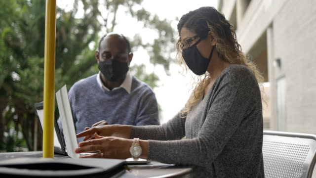 business partners working together on laptops with masks - administrator stock videos & royalty-free footage