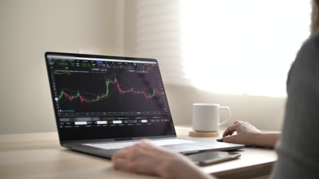 business people analyzing stock market data for trading on laptop - over the shoulder stock videos & royalty-free footage