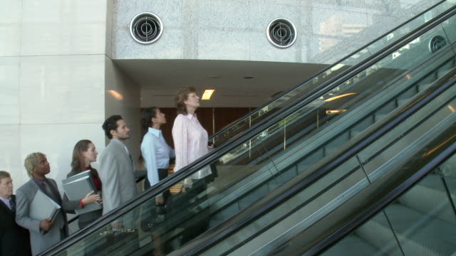 ws business people and person dressed in dog's costume traveling on escalator / bangkok, thailand - エスカレーター点の映像素材/bロール