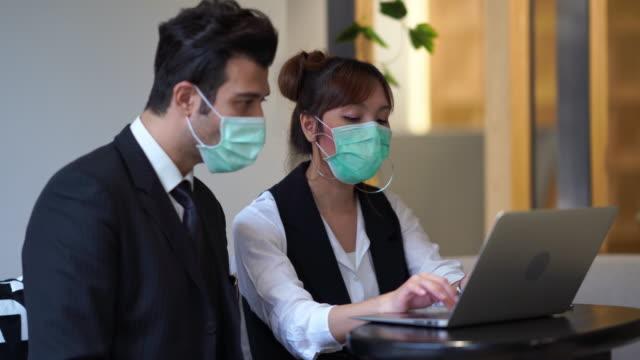 vídeos de stock, filmes e b-roll de pessoas de negócios estão trabalhando em laptop e usar máscara proteger poluição ou coronavírus - epidemic