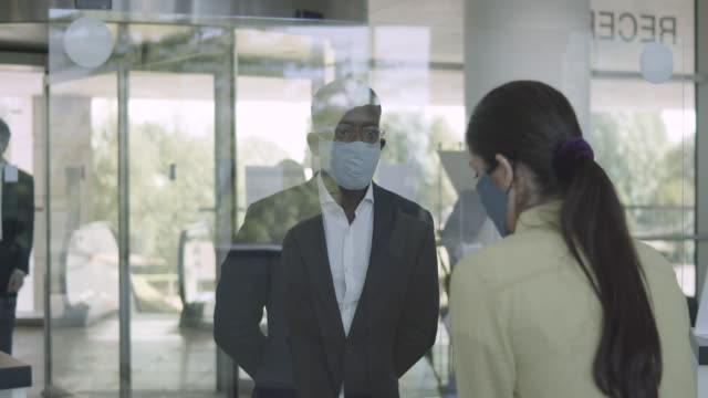 business people arriving in corporate office lobby wearing protective face mask - building entrance stock videos & royalty-free footage