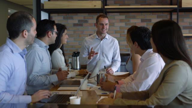Mensen uit het bedrijfsleven tijdens een vergadering gelode door de manager alle kijken gelukkig