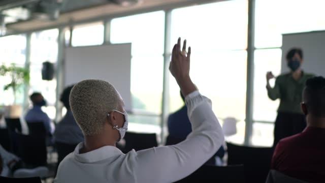 vídeos de stock e filmes b-roll de business people attending a seminar with social distancing and face mask - aplanar a curva