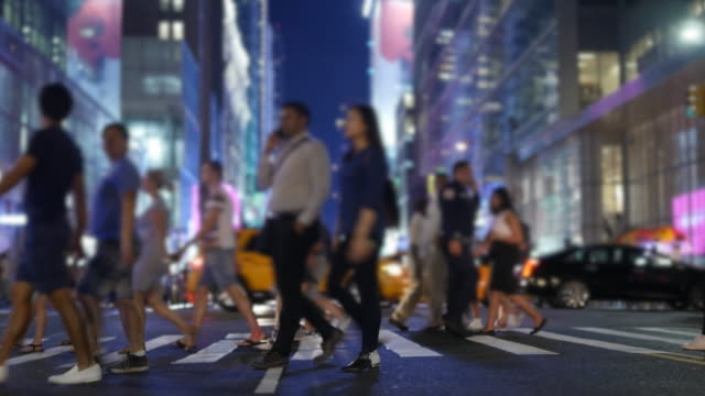 business people commuting on crowded street in the city. new york rush hour scene of anonymous pedestrians walking - 横断歩道点の映像素材/bロール