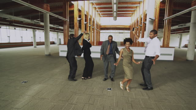 vidéos et rushes de ws ds business people dancing in empty office, squamish, british columbia, canada - collègue