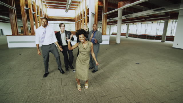 vidéos et rushes de ws business people dancing in empty office, woman showing cell phone to camera, squamish, british columbia, canada - collègue