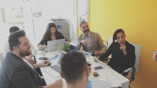 vidéos et rushes de gens d'affaires discuter au sujet des affaires dans la salle de réunion - âges mélangés