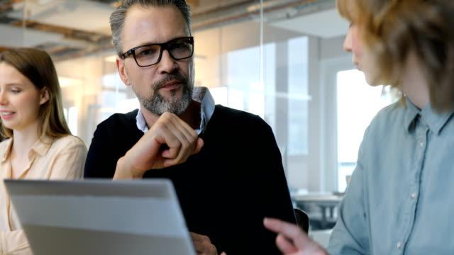 vidéos et rushes de gens d'affaires discuter au cours de la réunion - trois personnes
