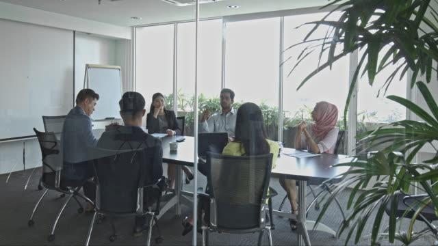 vidéos et rushes de gens affaires discutent en pension en chambre au bureau - origine ethnique
