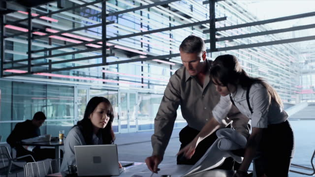 ms business people discussing over blueprint in cafeteria, los angeles, california, usa - berufliche partnerschaft stock-videos und b-roll-filmmaterial