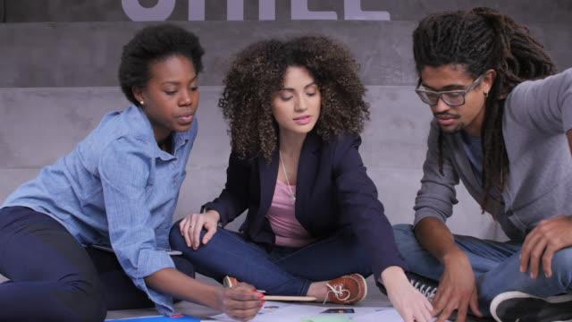 オフィスのレポートを論議しているビジネス人々 - 床に座る点の映像素材/bロール