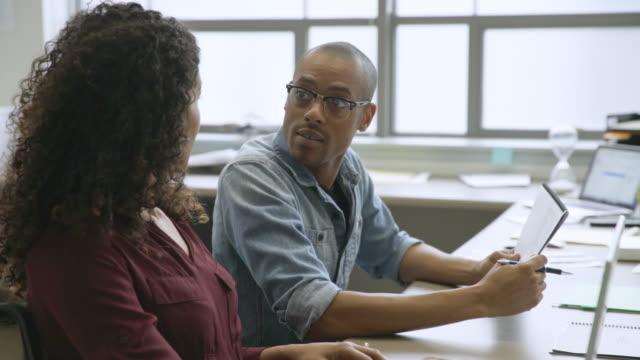vídeos de stock e filmes b-roll de business people discussing paperwork in startup office - fazer um favor