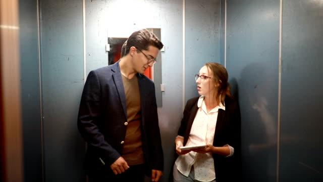 vídeos y material grabado en eventos de stock de empresarios hablar de trabajan en un ascensor - ascensor