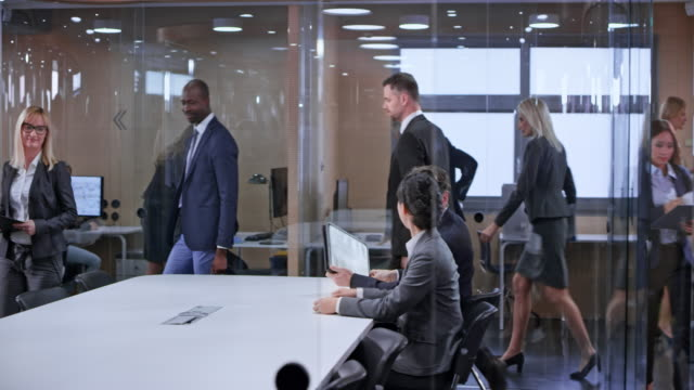 ds business people entering the glass conference room and sitting down - sala conferenze video stock e b–roll