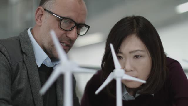 vidéos et rushes de business people examining wind turbine models in office - modèle réduit