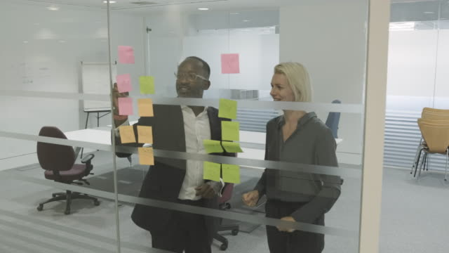 business people executives in meeting room using adhesive notes on window for corporate strategy - two people stock-videos und b-roll-filmmaterial
