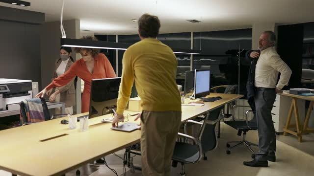 Pessoas de negócios terminando o trabalho no escritório tarde da noite durante a pandemia