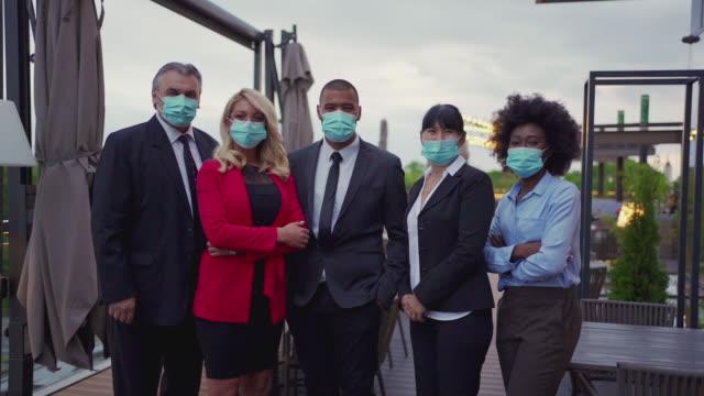 uomini d'affari che seguono le misure di protezione raccomandate durante una pandemia - abbigliamento da lavoro formale video stock e b–roll