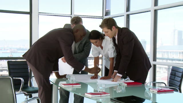 ms business people gathered around table with plan, cape town, south africa - tre quarti video stock e b–roll