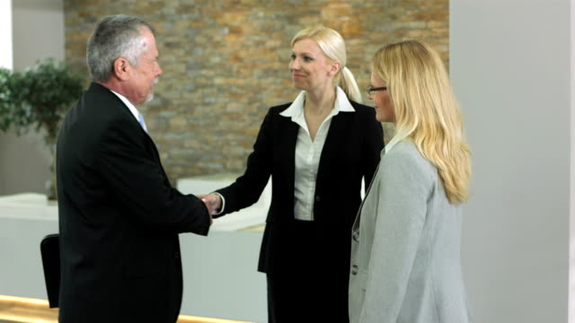ms business people greet in the lobby - lobby stock videos & royalty-free footage