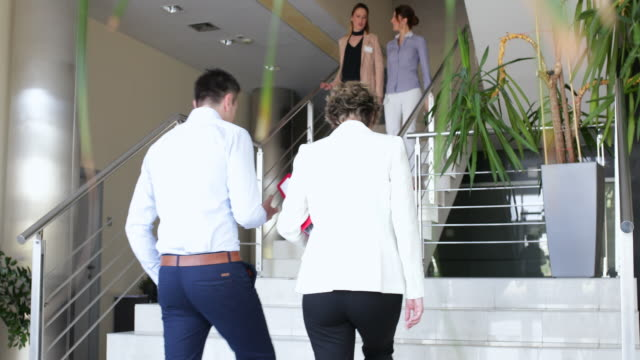 Business people greeting each other on the stairs