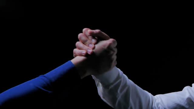 ビジネスの人々は一緒に握手をし、黒い背景に関する会議を終えます。お祝い, 成功, チームワーク, コラボレーション , サポート, 一体感, ビジネスエチケット, お祝い, 合併, 買収の概念.握� - 強さ点の映像素材/bロール